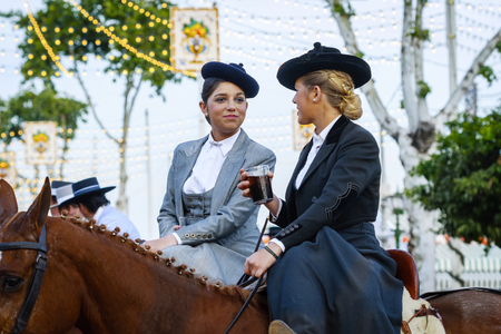 Seville, Spain - April 28, 2015: Two amazons wearing traditional Andalusian uniforms at the Aprils Fair of Seville. The Seville Fair Feria de abril de Sevilla is one of most important celebration of the city, it begins one or two week after easter Holy