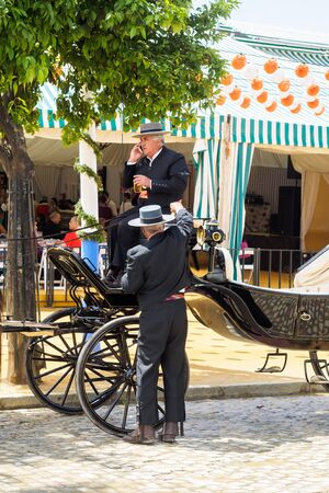 tradional: Seville, Spain - April 23, 2015: Carriage drivers dressed in tradional traje corto with casetas behind. The Seville Fair Feria de abril de Sevilla is one of most important celebration of the city, it begins one or two week after easter Holy Week