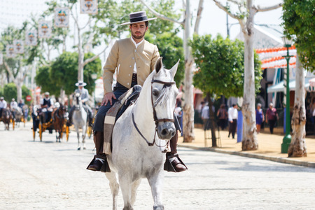 courteous: Seville, Spain - April 28, 2015: Horse rider taking a walk by the fair of Seville. The Seville Fair Feria de abril de Sevilla is one of most important celebration of the city, it begins one or two week after easter Holy Week Editorial