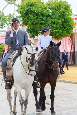 boy lady: Seville, Spain - April 29, 2015: Horse riders taking a walk by the fair of Seville. The Seville Fair Feria de abril de Sevilla is one of most important celebration of the city, it begins one or two week after easter Holy Weekand
