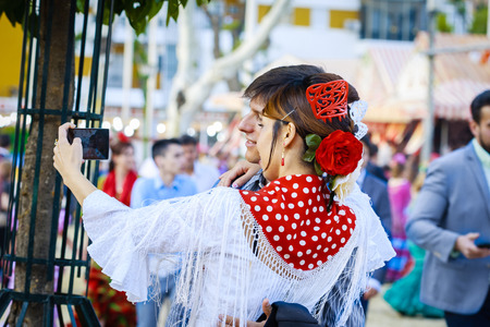 Seville, Spain - April 28, 2015: Japanese woman tourist dressed in traditional costumes at the Sevilles April Fair. The Seville Fair Feria de abril de Sevilla is one of most important celebration of the city, it begins one or two week after easter Holy