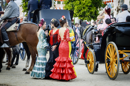 flamenco dress: Seville, Spain - April 28, 2015: Young women wearing traditional flamenco dress at the April Fair Seville . Editorial