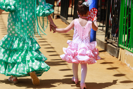 Seville, Spain - April 28, 2015: Mother and daughter in traditional dress walking alongside Casetas at the Seville Fair. The Seville Fair Feria de abril de Sevilla is one of most important celebration of the city, it begins one or two week after easter  Editorial