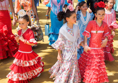 """Seville, Spain - April 23, 2015: Spanish girls in traditional dress walking alongside Casitas at the Seville Fair. The Seville Fair """"Feria de abril de Sevilla"""" is one of most important celebration of the city, it begins one or two week after easter Holy W Editorial"""