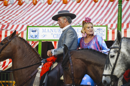 Seville, Spain - April 28, 2015: Couple in traditional dress riding at the April Fair Seville. The Seville Fair Feria de abril de Sevilla is one of most important celebration of the city, it begins one or two week after easter Holy Week Editorial