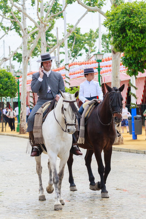 boy lady: Seville, Spain - April 29, 2015: Horse riders taking a walk by the fair of Seville. The Seville Fair Feria de abril de Sevilla is one of most important celebration of the city, it begins one or two week after easter Holy Week Editorial