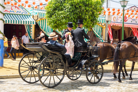 horse drawn carriage: Seville, Spain - April 23, 2015: People in traditional dress travelling in a horse drawn carriage at the Seville Fair. The Seville Fair Feria de abril de Sevilla is one of most important celebration of the city, it begins one or two week after easter Ho