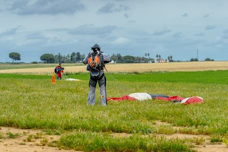 aerodrome: Seville, Spain - May 7, 2016: Skydiver unfasten his parachute after landing. Skydive Spain is the skydiving center located at La Juliana Aerodrome, about 20 km southwest of Seville, Spain. At Skydive Spain they fly up to 15,000ft, the highest altitude in  Editorial