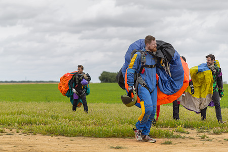 aerodrome: Seville, Spain - May 7, 2016: Skydivers carries a parachute after landing. Skydive Spain is the skydiving center located at La Juliana Aerodrome, about 20 km southwest of Seville, Spain. At Skydive Spain they fly up to 15,000ft, the highest altitude in Eu