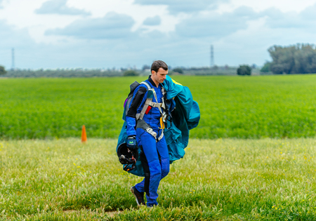 aerodrome: Seville, Spain - May 7, 2016: Skydiver carries a parachute after landing. Skydive Spain is the skydiving center located at La Juliana Aerodrome, about 20 km southwest of Seville, Spain. At Skydive Spain they fly up to 15,000ft, the highest altitude in Eur