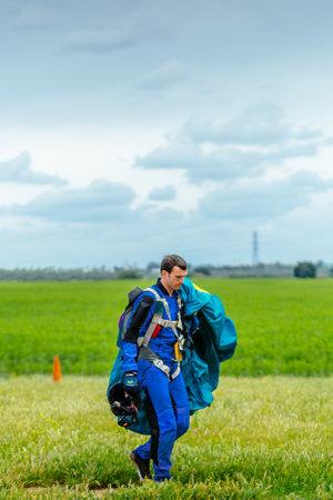 caida libre: Sevilla, España - 7 may, 2016: paracaidista lleva un paracaídas después de aterrizar. Skydive España es el centro de paracaidismo situado en La Juliana aeródromo, a unos 20 km al suroeste de Sevilla, España. En Skydive España vuelan hasta 15.000 pies, la altitud más alta en Eur Editorial