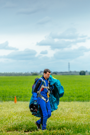 Seville, Spain - May 7, 2016: Skydiver carries a parachute after landing. Skydive Spain is the skydiving center located at La Juliana Aerodrome, about 20 km southwest of Seville, Spain. At Skydive Spain they fly up to 15,000ft, the highest altitude in Eur