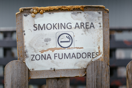 a public notice: Aged smoking area sign with snails glued