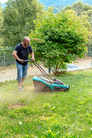 grass cutting: Man Mowing the lawn Stock Photo