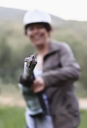 diameter: Smiling woman holding hammer drill of the big diameter. Selective focus