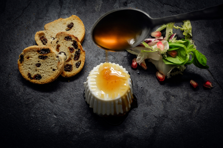 breackfast: Fresh cheese and Honey with salad of fresh vegetables and pomegranate on dark slate stone