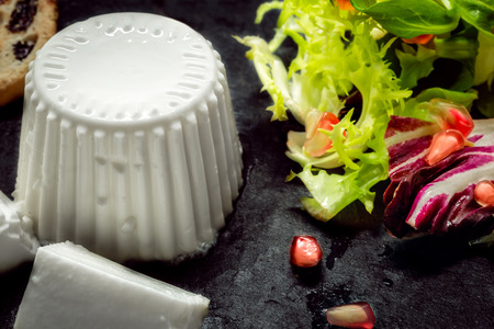 breackfast: Close up of Fresh cheese with salad of fresh vegetables and pomegranate on dark slate stone