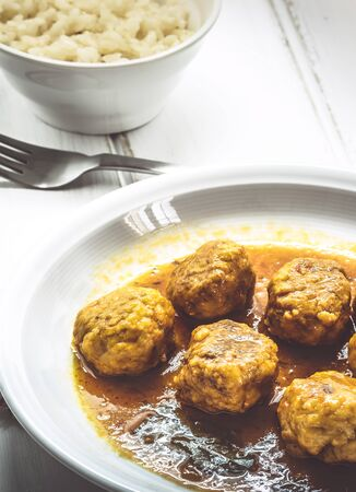 Homemade Meatballs in curry sauce on rustic wood background