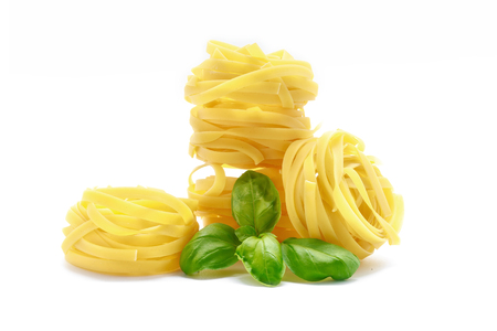 Fettuccine pasta with basil on white background