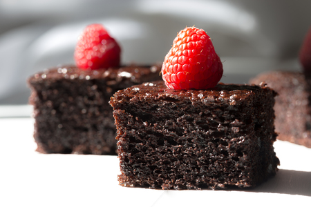 Dark chocolate cake decorated with raspberries