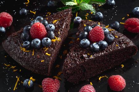 Close up of dark chocolate cake decorated with raspberries. Stock Photo
