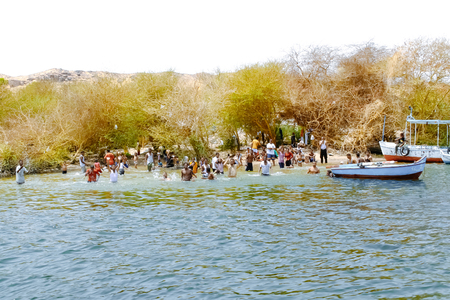 Aswan, Egypt - August 19, 2006: People swim in the Nile river. Aswan, Egypt. Aswan is a busy market and tourist center located just north of the Aswan Dams on the east bank of the Nile at the first cataract