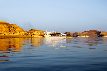 Lake Nasser, Egypt - August 17, 2006: Luxury cruise ship at lake Nasser. The statue of Ramses II and others, at Abu Simbel Temple, look out over Lake Nasser and tourists can enjoy the view from their cruise ship.