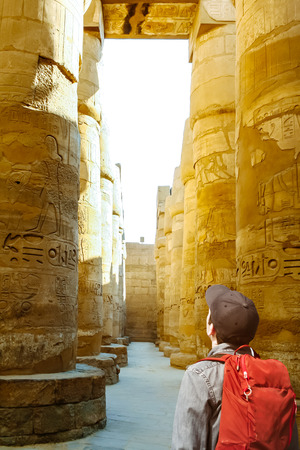 Tourist watching the columns of the hypostyle hall of Karnaks temple in Luxor, Egypt.