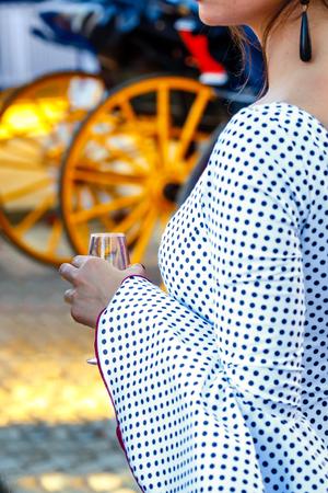 Hermosa mujer vestida de flamenca y sosteniendo un vaso de jerez fino. Concepto de viaje español Foto de archivo - 78775577