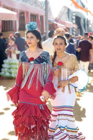 Sevilla, España - 02 de mayo de 2017: Mujeres jóvenes y hermosas vestidas con trajes tradicionales en la Feria de Abril de Sevilla. Foto de archivo - 78729443