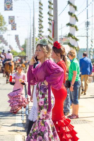 Sevilla, España - 02 de mayo de 2017: Hermosas mujeres vestidas con trajes tradicionales en la Feria de Abril de Sevilla. Foto de archivo - 78729448