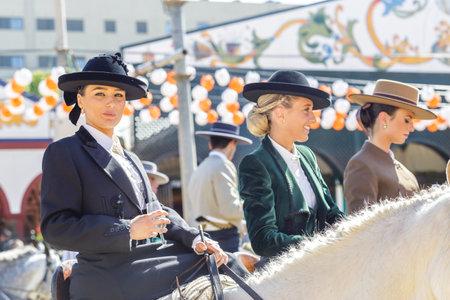 Sevilla, España - 02 de mayo de 2017: Hermosas mujeres jóvenes a caballo y celebrando la Feria de Abril de Sevilla. Foto de archivo - 78729449
