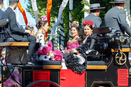 Seville, Spain - May 02, 2017:  Young and beautiful women on a horse drawn carriage during the the April Fair of Seville.