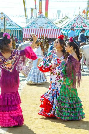 Sevilla, Spanien - 2. Mai 2017: Junge Frauen kleideten in den bunten Kleidern an der Sevilla-April-Messe in Spanien an Standard-Bild - 78729452