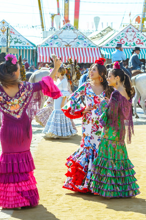 Seville, Spain - May 02, 2017: Young women dressed in colourful dresses at the Seville April Fair in Spain Redakční
