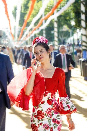 Sevilla, España - 02 de mayo de 2017: Hermosa mujer vestida con trajes tradicionales y hablando por teléfono móvil en la Feria de Abril de Sevilla. Foto de archivo - 78729453