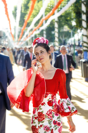 Seville, Spain - May 02, 2017:  Beautiful Woman dressed in traditional costumes and speaking by mobile phone at the Sevilles April Fair. Editorial