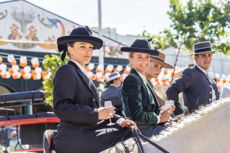 Sevilla, España - 02 de mayo de 2017: Hermosas mujeres jóvenes a caballo y celebrando la Feria de Abril de Sevilla. Foto de archivo - 78729457