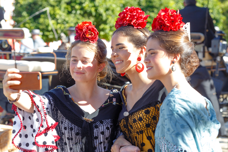 Seville, Spain - May 02, 2017: Three Beautiful women taking selfie photo at the Seville's April Fair.