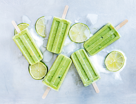 Yogurt and lime popsicles on ice cubes over gray tray background. Refreshing and Healthy summer dessert