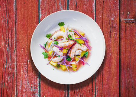 Refreshing dish of fish marinated in citrus juice. Shrimp and Mango Ceviche on red wooden table. Diet and healthy food concept Stock Photo