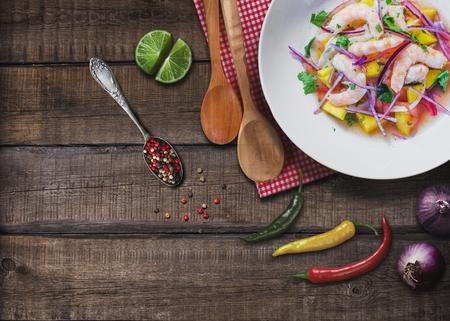 Refrescante plato de pescado marinado en jugo de cítricos en mesa de madera. Ceviche de camarones y mango. Dieta y concepto de alimentos saludables Foto de archivo - 82333874