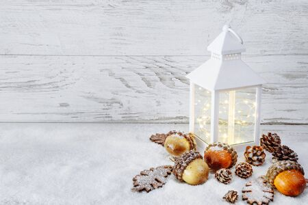 Christmas decoration. Lantern On Snow with acorns and oak leaves
