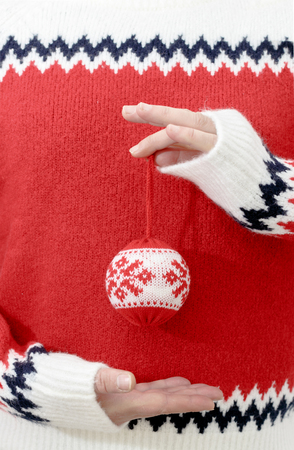 Person in winter sweater holding Christmas balls in hands. Close up, copy space, vertical composition.