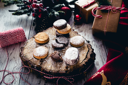 Traditional Spanish Christmas candy. Andalusian Shortbread cookies (Polvorones) on oak tree trunk. Polvoron  is a type of heavy, soft and very crumbly Spanish shortbread made of flour, sugar, milk, and nuts, especially almonds. They are produced mostly in Andalusia, Spain.