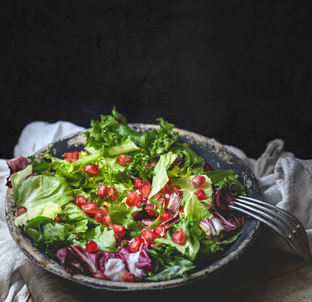 Green vegan salad in bowl with endive, arugula, mixed lettuces and pomegranate. Dieting, vegan food concept.