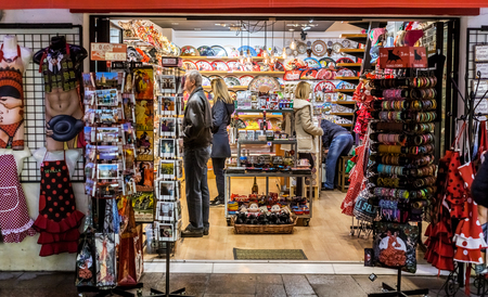 Seville, Spain - January 13, 2018: Young people shopping. People in the sales looking at  store. Twice a year in Spain shoppers are treated to an end-of-season sale period, called las rebajas, in which goods can be purchased at a significant discount.