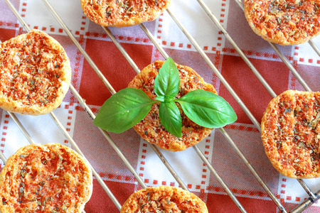 Mini baked pizzas with tomato, oregano and basil on red and white checkered tablecoth.