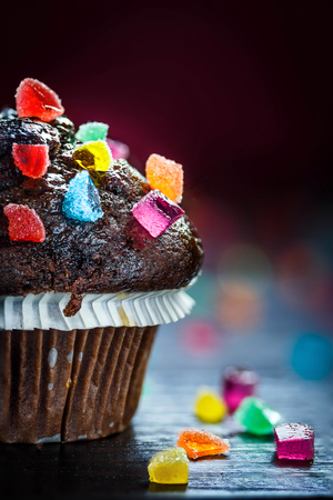 Close up of Chocolate Muffin with candies on wooden table with bokeh background. Selective focus.