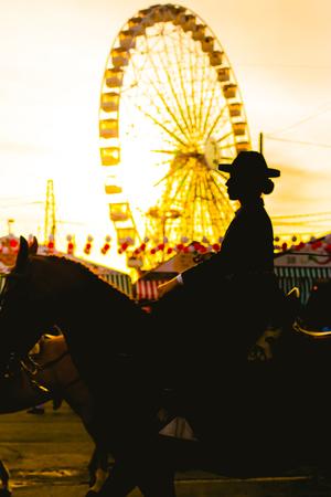 Silhouette of woman horse raide at sunset. Seville's April Fair. Spanish Culture Foto de archivo - 95582884